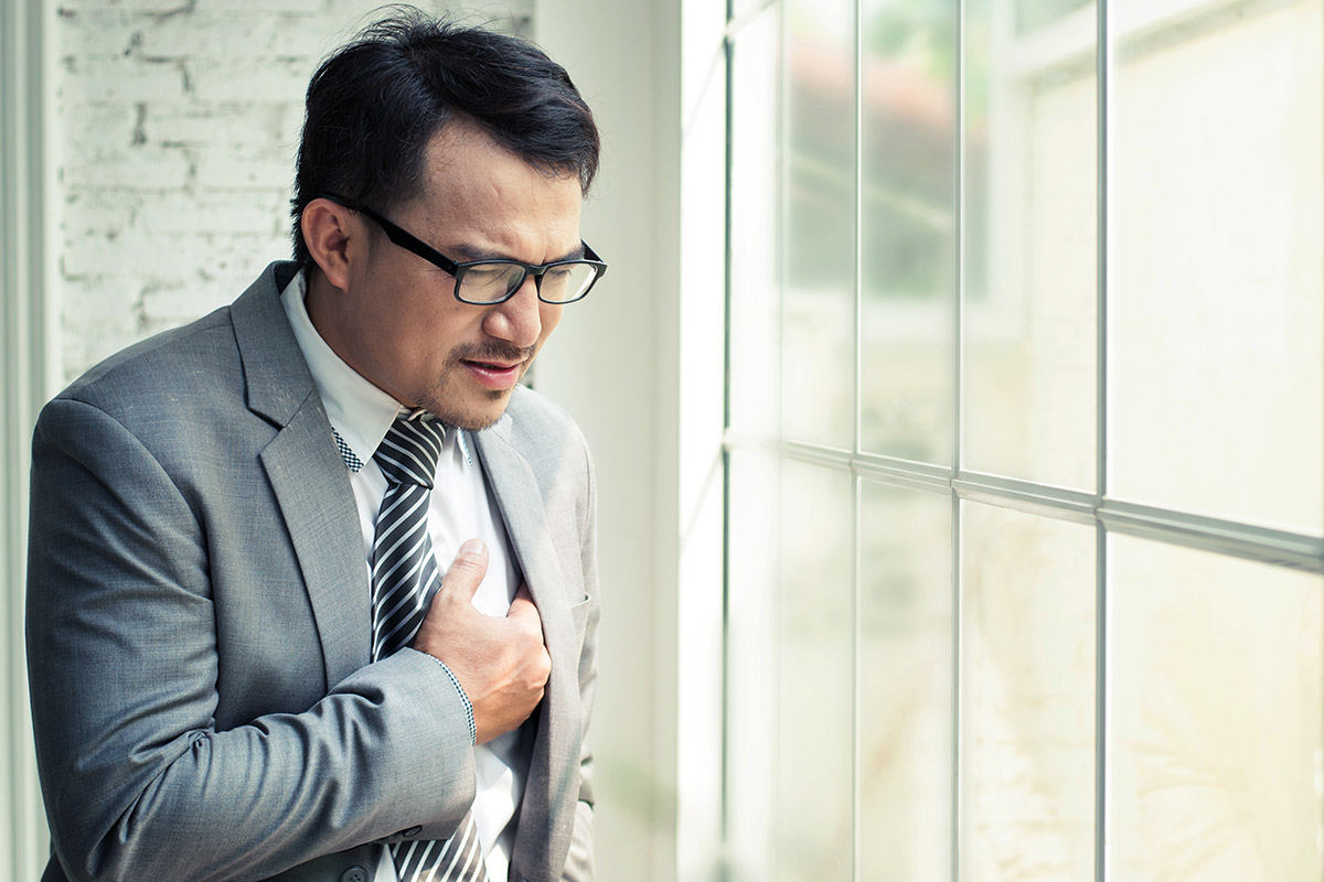 Asian man in business suit holding chest