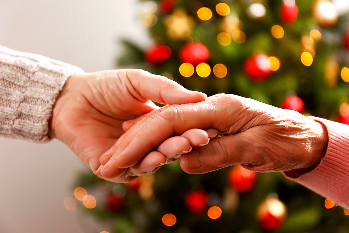 Holding hands in front of Christmas Tree