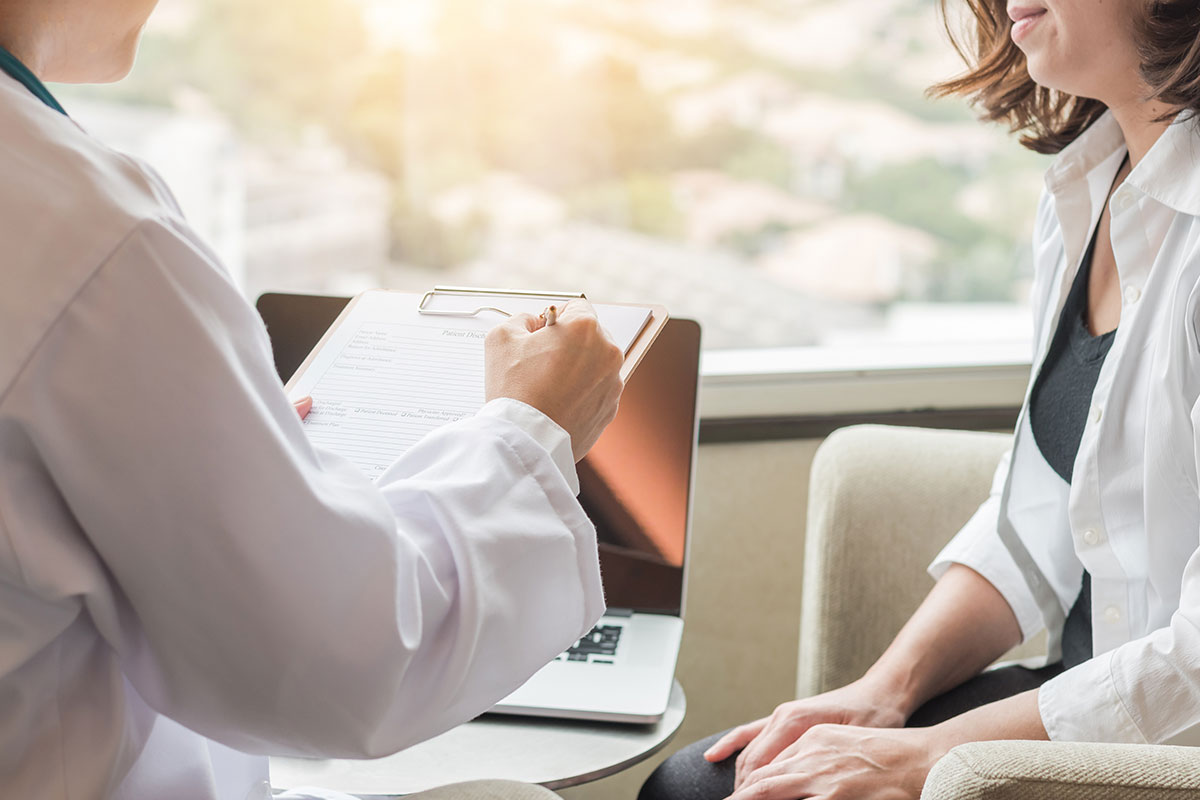 Doctor writing on clipboard while sitting across from woman