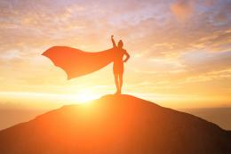 Silhouette of a person wearing a cape that is fluttering in the breeze as they stand on top of a hill at sunset.