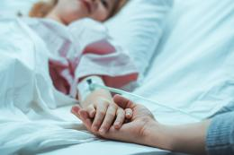 Child in a hospital bed holding an adult's hand.
